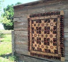 """A wonderful primitive quilt pattern by Primitive Pieces by Lynda.  This quilt measures 64 inches with pansies in the middle of each 15"""" block."""