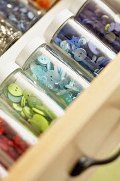 Organize buttons by color and store them in transparent, matching containers. Hide the jars in a pullout drawer to minimize clutter. Meredith Corp.