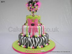 Three tier teenage birthday cake in a zebra stripe, candy strip and lime green. Bright pink sugar bow , polka dots with age and sugarballs. Finished with a matching wired starburst cake topper