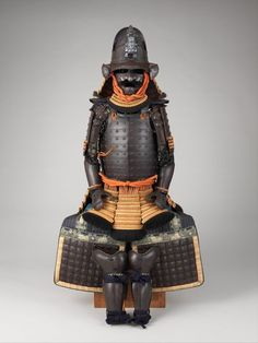 Samurai armor (Gusoku), 18th century. Iron, lacquer, silk, gilt copper. Dimensions: as mounted: H. 57 3/4 in. (146.7 cm). This cuirass and shoulder guards (sode) formed of large iron plates rather than traditional lamellae (small, narror iron plates) reveal European influence and the concurrent introduction of firearms, which necessitated solid, bulletproof plates. -The Metropolitan Museum-