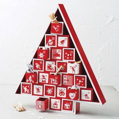 A gorgeous wooden Nordic style advent calendar with twenty four drawers stacked on top of each other in a Christmas tree shaped frame