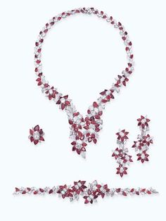 A RUBY AND DIAMOND SUITE, BY MOUAWAD; Comprising a necklace, a bracelet, ear pendants and a ring of floral design set with pear-shaped rubies and variously cut diamonds, mounted in 18k white gold, necklace 45.0 cm long, bracelet 18.0 cm long, ear pendants 6.0 cm long, ring size 6.