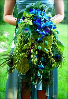 Long Cascading 1920s-style bridal bouquet from Spider Flower, is wild and wonderful with it's peacock feathers and blue and green cymbidium orchids.