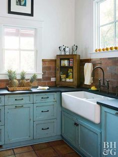 A swath of contrasting color around the perimeter of the kitchen can help people who are visually impaired navigate throughout the space. This wide band of brick tiles contrasts the blue-painted lower cabinets and the black laminate countertops.