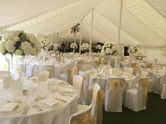Tall flute vase table centrepiece, white hydrangeas and Roses and Gypsophila. White and gold marquee wedding.