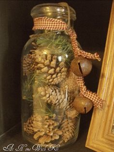 Rustic Christmas Decor- a jar full of pinecones and evergreen sprigs. The gingham ribbon & old bells are perfect!