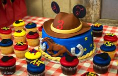 These Mickey Mouse Cowboy cake and cupcakes were for twin boys 3rd birthday celebration.  The fondant cake featured a galloping horse, horseshoes, stars and a cowboy hat with Mickey ears. The red, yellow and blue cupcakes were embellished with Mickey ears and the boys initials.