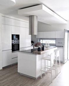 Na każdej ścianie kuchni znajdują się zamknięte szafki, jednak ich biały kolor niweluje ewentualny efekt przytłoczenia. Zamiast tego we wnętrzu jest jasno i przyjemnie, a nieco surowa kolorystyka wyznacza elegancki charakter.