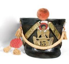 Shako de troupe de fusiliers du 13ème regt. d'infanterie de ligne. Fût en feutre noir garni d'une plaque à l'aigle de 1812 à chiffres percés. Jugulaires avec rosace à l'étoile. Pompon aurore, cordon bicolore aurore et rouge, crochets en étoile. Bien complet avec sa coiffe intérieure.