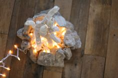 """Create a cozy indoor """"campfire"""" with string lights and a few natural elements. Get the info here!"""