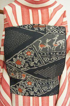 チャコール・ブラックの地に、壺や鳥やコヨーテや花唐草が古代の壁画のように織り出された、エキゾチッックムードただよう開き名古屋帯です。