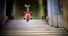 """Audrey Hepburn in the film """"Funny Face"""" descending the Duru Staircase (Louvre)in that red Givency gown. The Winged Victory behind her.       image from http://aviary.blob.core.windows.net/k-mr6i2hifk4wxt1dp-14031704/88e669f4-85ce-4679-8dd1-5e85aa321beb.png"""