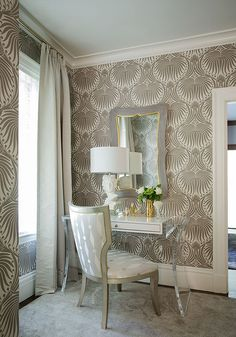 Gray contemporary bedroom donning walls covered in Farrow & Ball Lotus Wallpaper features a silver curved back vanity chair seated in front of…