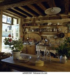 Rustic cottage kitchen with wooden table and shelving View Large Photo Image