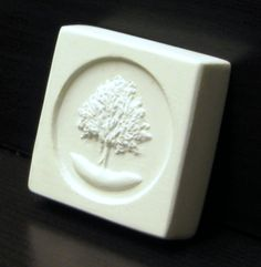 """Acquavena Guest Soap Bar Plaster Protoype. Square soap bar 1.75"""" x 1.75"""" x 0.5"""" thick with slightly rounded edges, inset design with raised company logo/artwork. Company located in Colorado, United States. www.acquavena.com"""