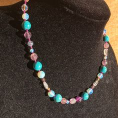 "Fun and flirty! The beautiful color play of purples, blues, and clear beads is sure to impress any jewelry lover! This 19"" beauty is strung on 19 strand beadalon gold tone wire with a gold tone lobster clasp. Features amazing artistry and quality beads!! The necklace features a"