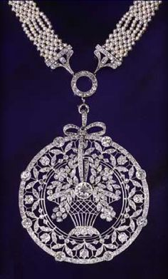 """platinum millegrain and diamond fittings is attached to an openwork platinum millegrain circular pendant, outlined by a diamond border. This encloses a tall basket of diamond flowers centred on a collet diamond, and joined to the necklace by a ribbon tied into a bow, and surrounded by an openwork garland of flowers and leaves on """"knife-edge"""" wires. C. 1910"""