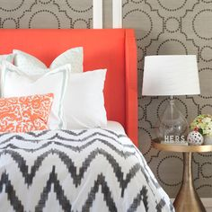 Love it all!  Bright, coral upholstered headboard, chevron duvet, and grasscloth nailhead feature wall!  Sarah M. Dorsey design  #chevron #coralgrey #bedroom #featurewall