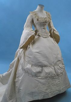 """French 3-piece ivory silk faille reception/wedding gown dating to the third quarter of the 19thc. A marvel of fine French dress making construction and hand stitching, fascinating details through out all three pieces and made in the finest materials. With labels both on the waist petersham and the interior of one of the skirt's waist band, that reads """"Grands Magasins, Rue de la Paix""""."""