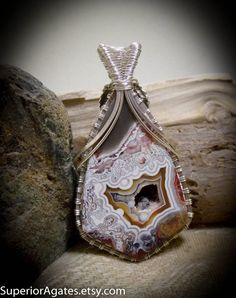 This is a beautiful hand cut cabochon, of genuine Mexican Crazy Lace Agate. This stone is just gorgeous with its mixed coloring, and gorgeous patterns. Elegantly wire wrapped in sterling silver filled wire, with .999 fine silver weaves, adorned with a silver plated flower, leaves, and a genuine Agate bead, this larger pendant will make the perfect addition to your collection. Over all pendant size : 2 3/8 inches tall Gem stone size : 1 7/8 x 1 1/4 inch  SEE THE REST OF MY ITEMS…