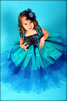 https://flic.kr/p/7jTi8y | Christmas Peacock TuTu Dress | Beautiful Peacock colors in vibrant blue,navy and teal. This teired tutu is full and super fluffy and adorned with elegant peacock feathers.   Photo by Rockstarr
