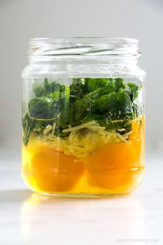 Side view of mason jar with ingredients layered ready for cooking - raw eggs, grated cheese, spinach