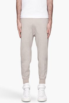Neil Barrett Pale Taupe Skinny Fit Elasticized Track Pants -  Neil Barrett Pale Taupe Skinny Fit Elasticized Track Pants Neil Barrett Slim_fit low_rise track pants in pale taupe. One pocket at back with mock scoop pockets at front. Elasticized waistband with drawstring. Ribbed knit ankle cuffs. Tonal stitching. Price $495.00 Click HERE for more Information