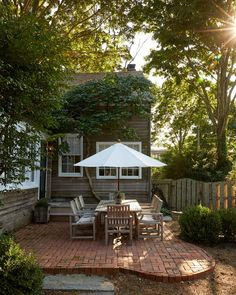 A manicured backyard—complete with a simple brick patio and contemporary teak furnishings—is great for entertaining in the summer months, though the couple will live in the home year-round.