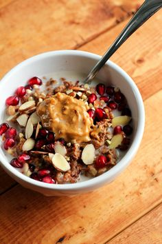 Buckwheat & chia oatmeal with melted chocolate chips, pomegranate seeds, sliced almonds, coconut-almond milk, and peanut butter.