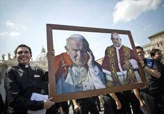 Dos jóvenes sacerdotes pertenecientes a los Legionarios de Cristo sostienen una imagen del papa Juan Pablo II y Juan XXIII (Foto: EFE)