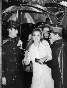 Catherine Deneuve escorted by gendarmes in 57th Street (New York) for the American premiere of The Umbrellas of Cherbourg, December 1964. Photo: Hulton Archive/Getty Images.
