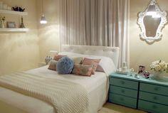 a mesa lateral azul são duas mesas de cabeceiras unidas por um tampo também pintado, o espelho completa a decoração. A iluminação pendente trás o clima romântico para o quarto.