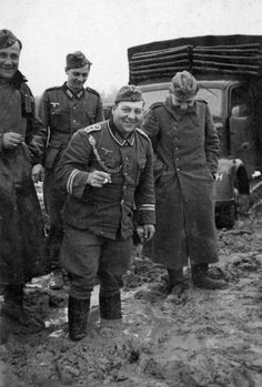 Russian mud was no fun , but these German soldiers wear a smile for the photographer . Note the NCO in the center , wearing a braid for marksmanship . This is unusual - braids were never worn with field uniforms . Somewhere in Russia 1942