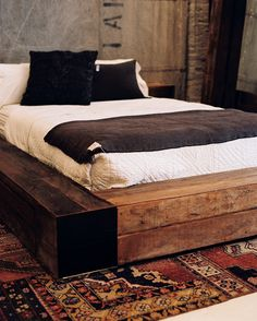 Bedroom Photo - A low wooden bed with white and gray bedding atop a patterned rug
