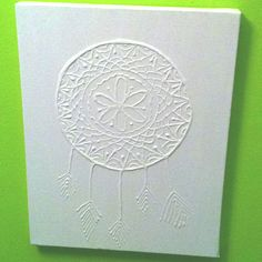 Dream catcher outlined in puffy paint on a canvas and painted entirely white.
