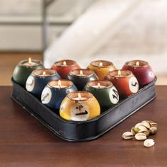 Pool Ball Candle Holder:  Our Pool Ball Candleholder is sure to provide the perfect ambiance for your bar, game room, or man cave. Designed to resemble a racked set of billiard balls, this decorative metal candleholder features ten distressed balls painted in traditional colors. @ryanmelissastephens. You need this for the downstairs bar!