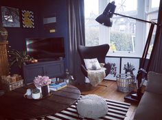Corner of my living room painted in Farrow and Ball Stiffkey Blue. Giant Anglepoise lamp and monochrome prints and rug.