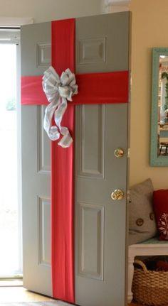 Para no recurrir a la típica corona de Navidad, esta lazada en la puerta es una alternativa bonita y elegante.