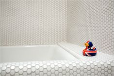 """""""inexpensive ceramic pennyround tiles by Dal-Tile were 'draped' around the tub's edge"""""""