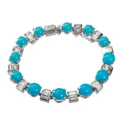 A circa 1960 diamond and cabochon turquoise in platinum bracelet. 12 carefully polished turquoise sit between half-round platinum settings filled with baguette shaped diamonds.