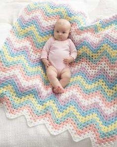 Crochet this zig-zag blanket in the rainbow colors of Bernat Giggles..