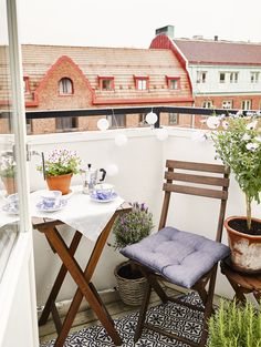 Small outdoor space with folding chair and small potted plants