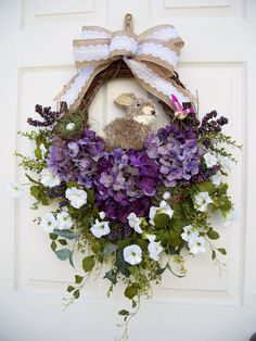 Easter and Spring decorating are always fun after a long winter. A womderful way to greet your guests is with a wreath that has all the elements of Spring, from Spring flowers to wild life. I love using nature as inspiration in my wreaths and swags and this one is no exception. A furry bunny is tucked in the center flanked by two bird nests with eggs, and even a little hummingbird is buzzing around. Three pretty purple variegated hydrangeas add a nice soft touch. White morning glories and…