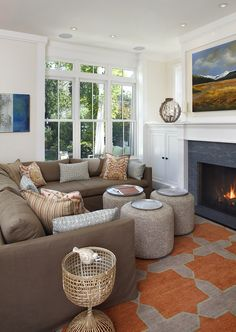 Large-scale geometric rug, comfy sectional, classic built-ins, mantel, trim, windows.  Throw pillows.