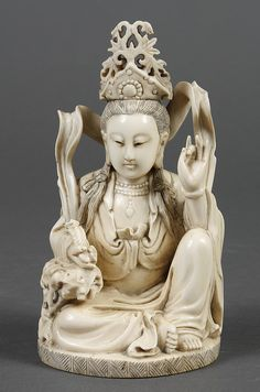 "CARVED IVORY FIGURE OF SEATED QUAN YIN - Statue holds a ruyi in right hand. She is seated in a relaxed position with hand on knee and a scroll or ribbon floating above and behind her. Seal mark on base. Condition good; some cracking in surface. Pre-ban. 20th century. 6.5""H x 4""W x 4""D."