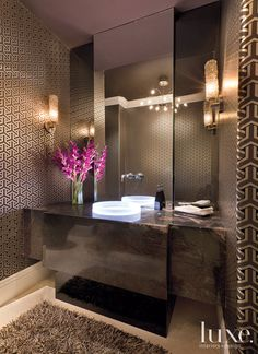 Lighting is a main focus of the residence, as seen in this powder room, where a Luminist vessel glows with its LED ring.