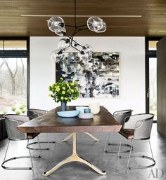 Jim Zivic chairs from Ralph Pucci International join a BDDW table beneath a Lindsey Adelman Studio light fixture in the dining area.