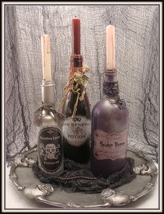 This DIY Halloween decoration potion bottles are made of spray painted wine bottles of varying sizes, and labels, twine, candle wax, and plastic toys.