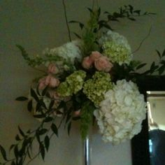 Eiffel tower vase with roses, hydrangeas, bells of ireland, and curly willow. Great centerpiece.