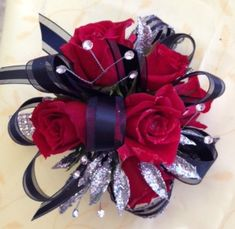 Wrist corsage includes red spray roses, black ribbon, silver leaves, rhinestones, and comes on a rhinestone band HC1307
